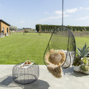 On a concrete patio sits a black wire ottoman beside a black wire hanging egg chair, with a sheepskin & raffia cushion sitting inside. A large green lawn is in the background.