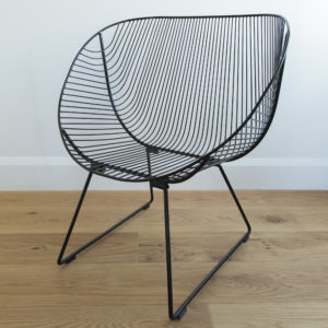 A mid century, 60's style, outdoor wire garden chair with curved edges, colour Black