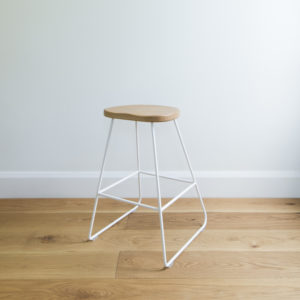 angle view of kitchen stool with white wire legs & a rounded solid oak seat