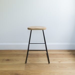 front view of kitchen barstool with black wire legs & organically rounded solid oak seat