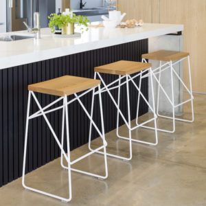 Modern scandinavian kitchen with three Oak and wire barstools sitting at the bench.
