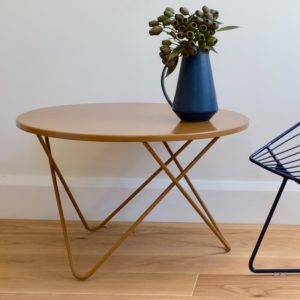 A round metal coffee table with 3 hairpin legs holds a blue jug of gum nuts