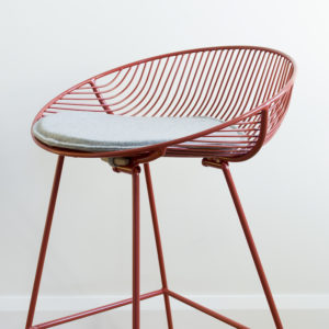 Grey, felted wool, cushion or pad on a red wire kitchen barstool