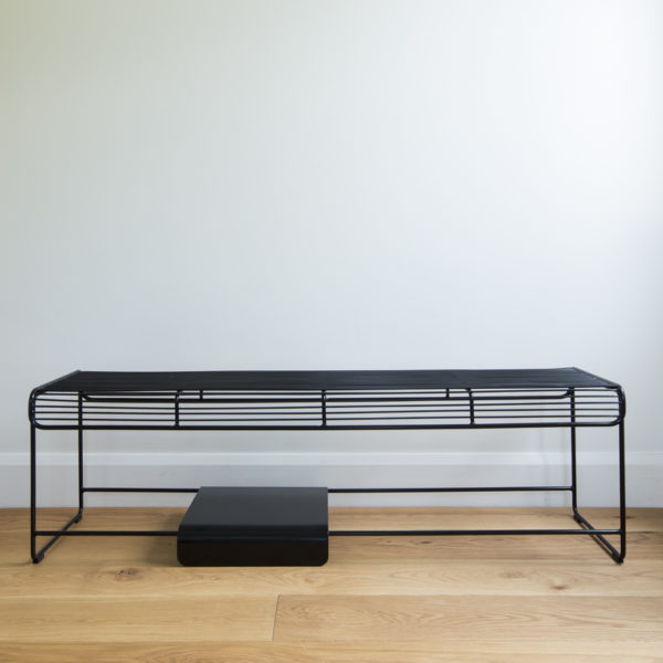 Black wire bench seat with a movable solid metal plate sitting on the bottom rungs
