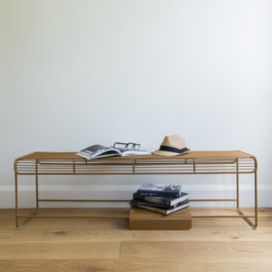 Wire bench seat with a separate metal plate that is being used to store books on bottom rungs