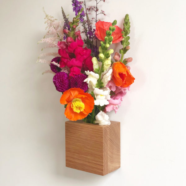 A square oak wall vase with flowers in it is attached to a wall